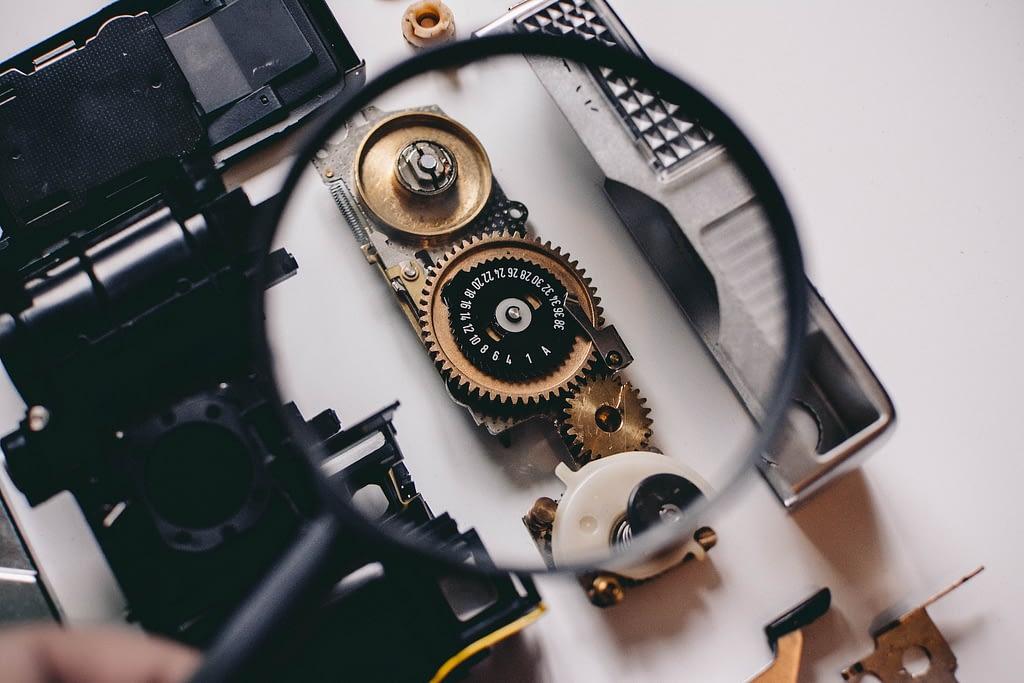 Magnifying glass showing cogwheels