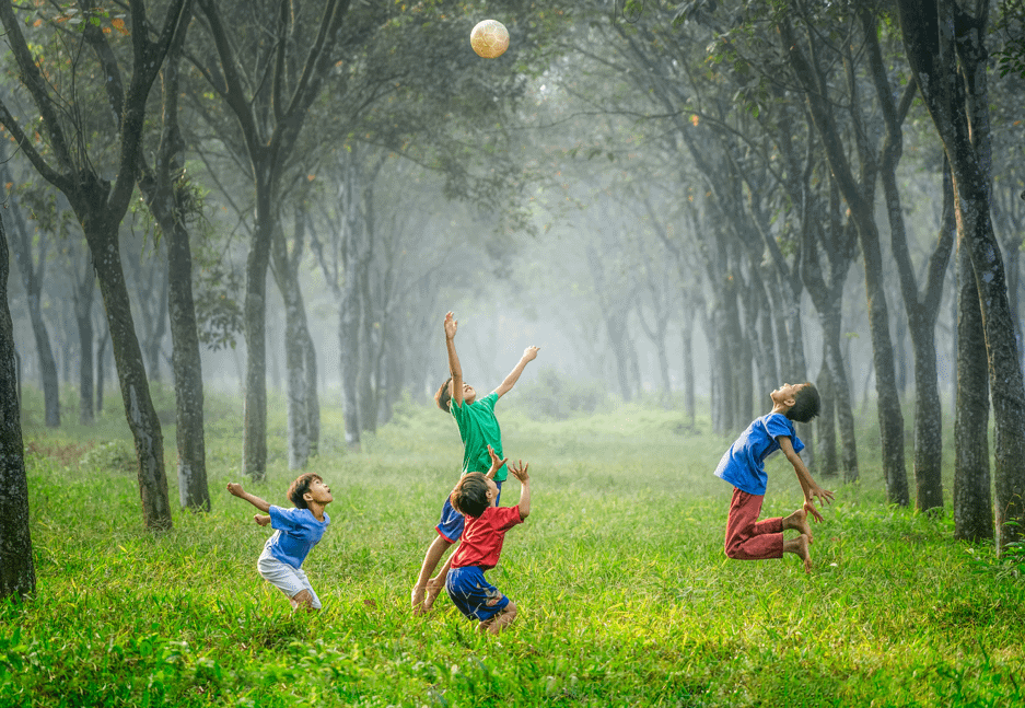 Kids jumping in the air in a lush, green forest