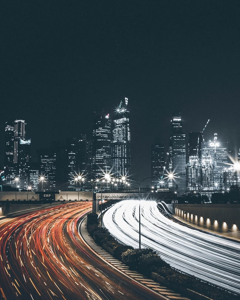 Streaks of light from cars with the city skyline as the backdrop