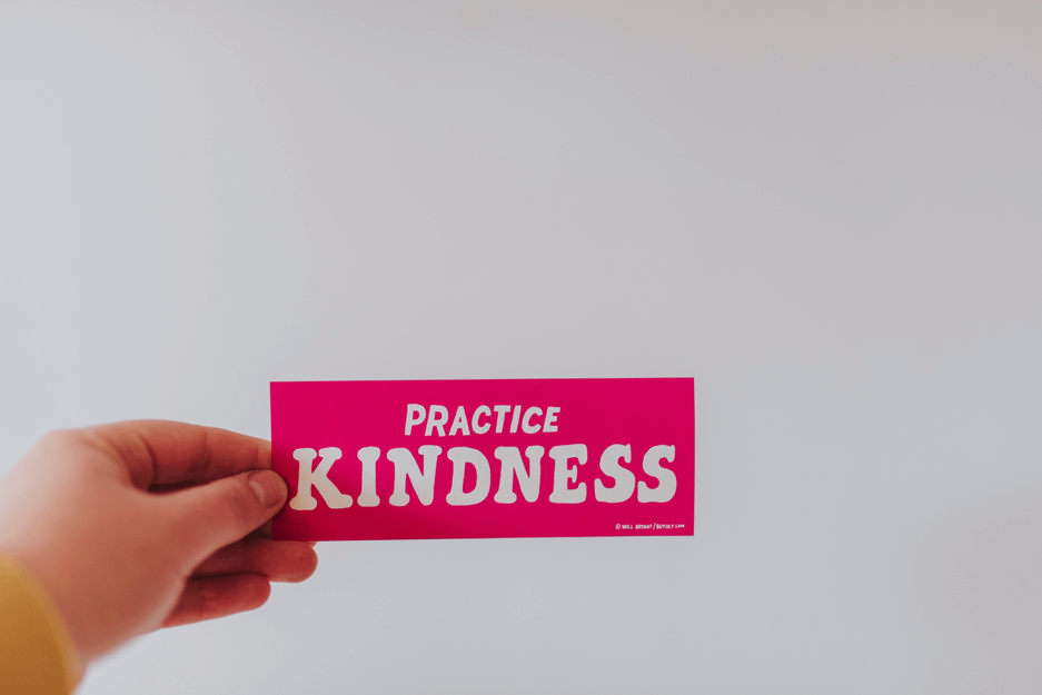 "Hand holding up a pink slip that says ""Practise Kindness"""