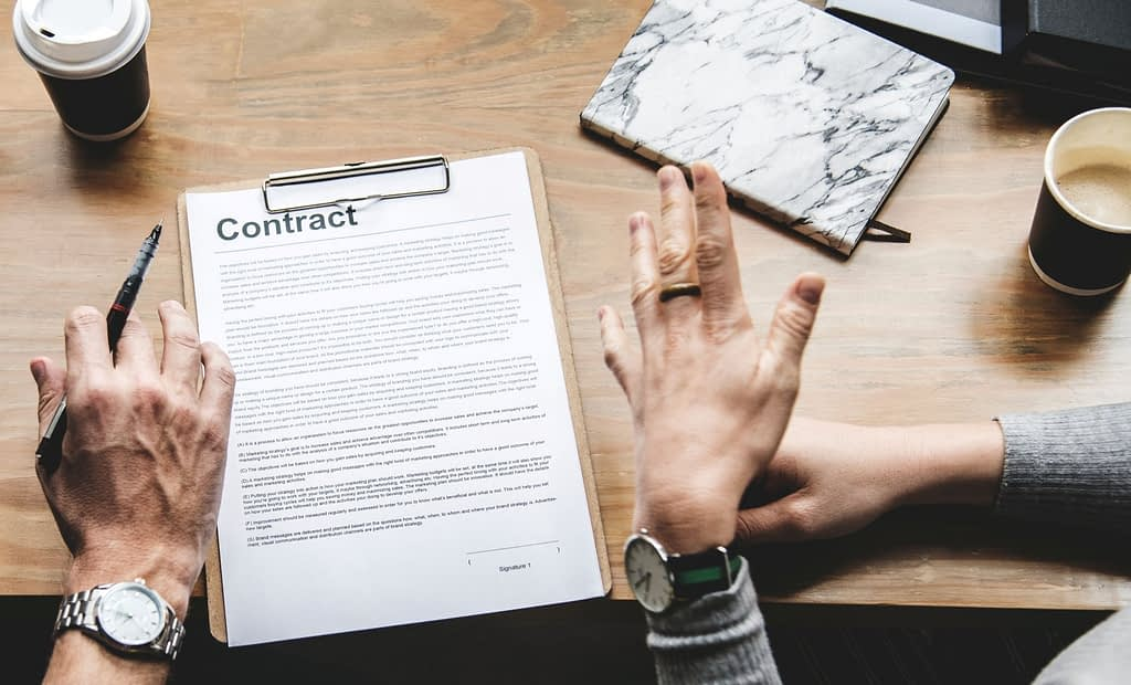 Paper titled Contract on a board on a table